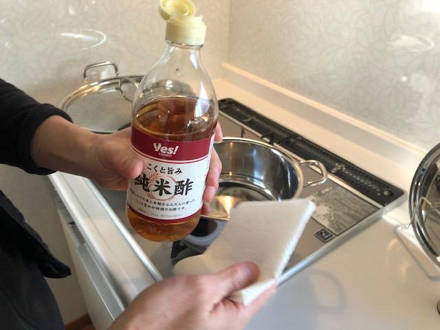 酢で小鍋を拭く様子